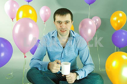 Man with cup in hands against of balloons