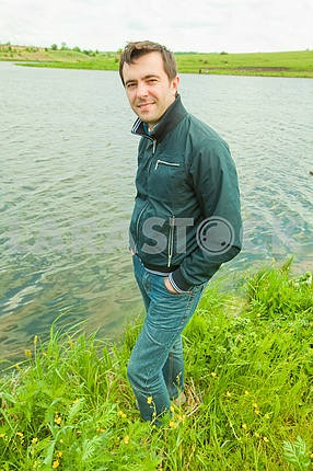 Happy young man stands near river in grass
