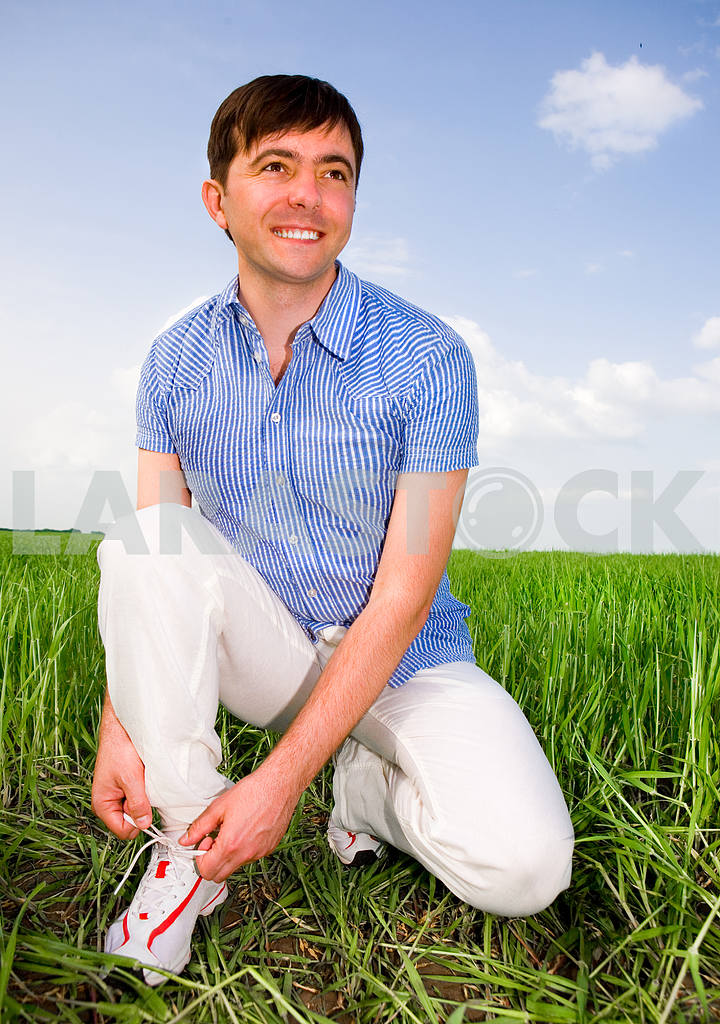 Man is Tying Laces In A Green Field — Image 10013