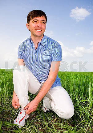 Man is Tying Laces In A Green Field