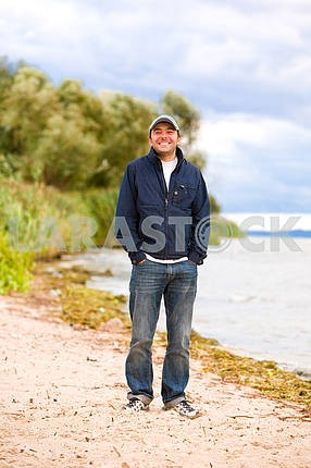 Young smile man on coast of river