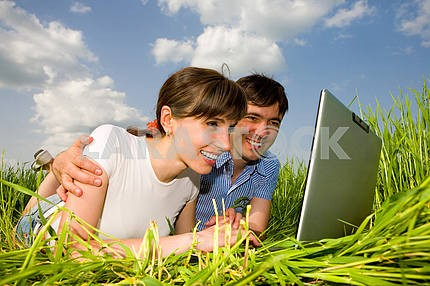 Happy couple on a laptop computer outdoors. Lay on the green gra