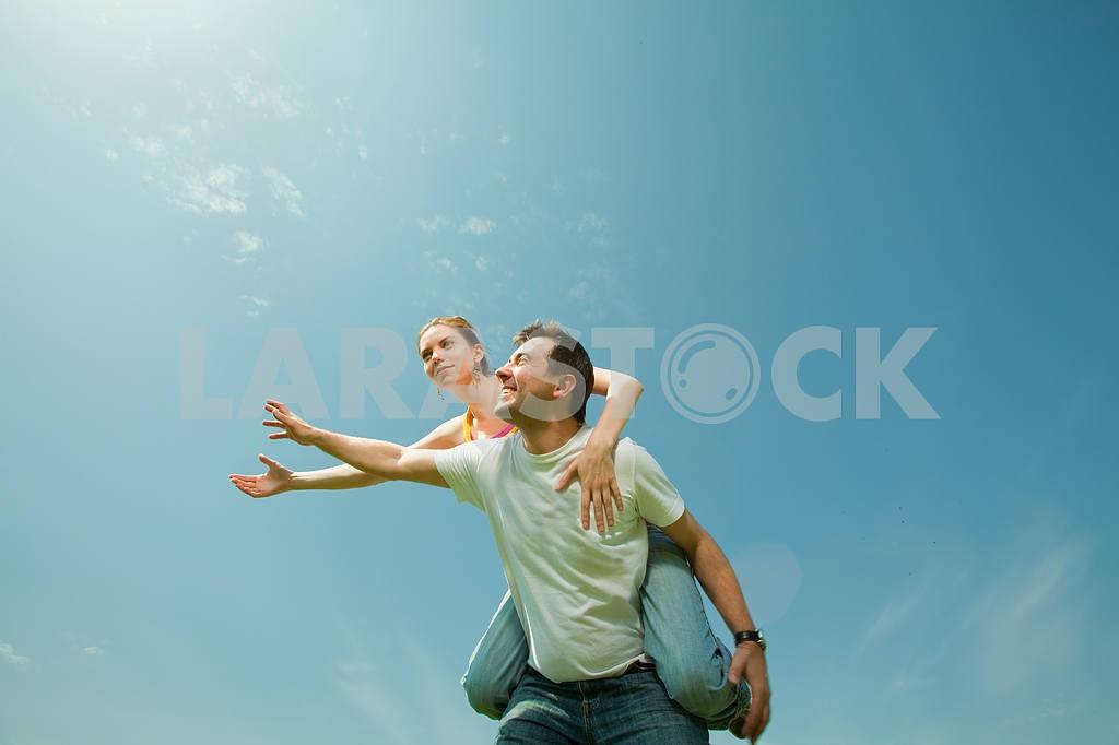 Молодые любви пара, улыбаясь в голубое небо — Изображение 10044