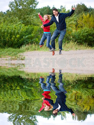 Happy Young Couple - jumping in the sky against a green tree