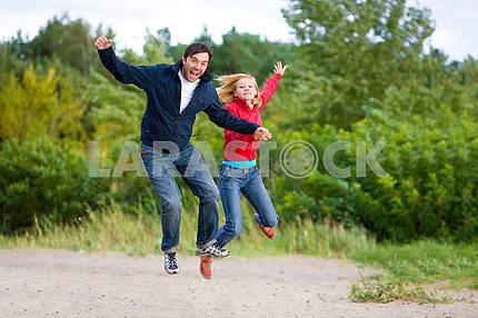 Счастливый молодая пара - прыжки в небо на зеленом дереве