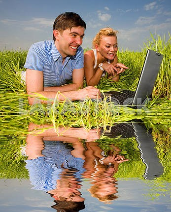 Casual happy couple on a laptop computer outdoors. Lay on the gr