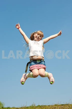 Little girl jumping against beautiful sky