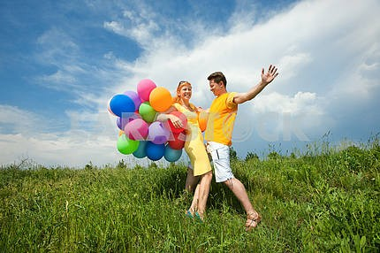 мужчина и женщина , играя с воздушными шарами против голубого неба