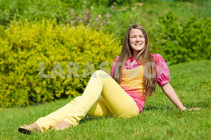 Pretty smiling girl open hands relaxing on green meadow. Soft fo