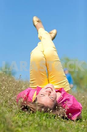 Довольно улыбается девушка расслабляющий на зеленый луг , полный цветов . Так