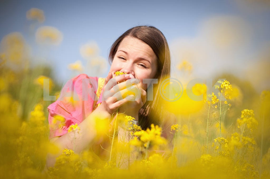 Pretty smiling girl relaxing on green meadow full of yellow flow — Image 11119