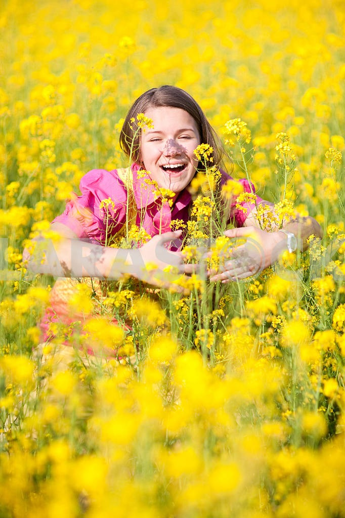 Pretty smiling girl relaxing on green meadow full of yellow flow — Image 11123