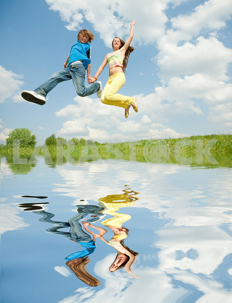 Girl and boy jumping. Reflected in Water — Image 11143