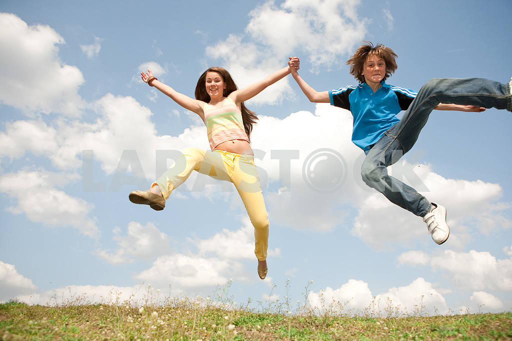Girl and boy jumping on meadow  smiling under blue sky — Image 11162
