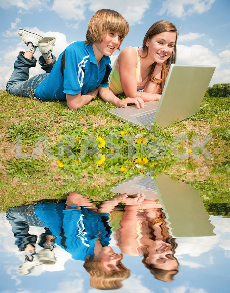 Two Smiling teenagers with laptop resting on meadow. — Image 11175