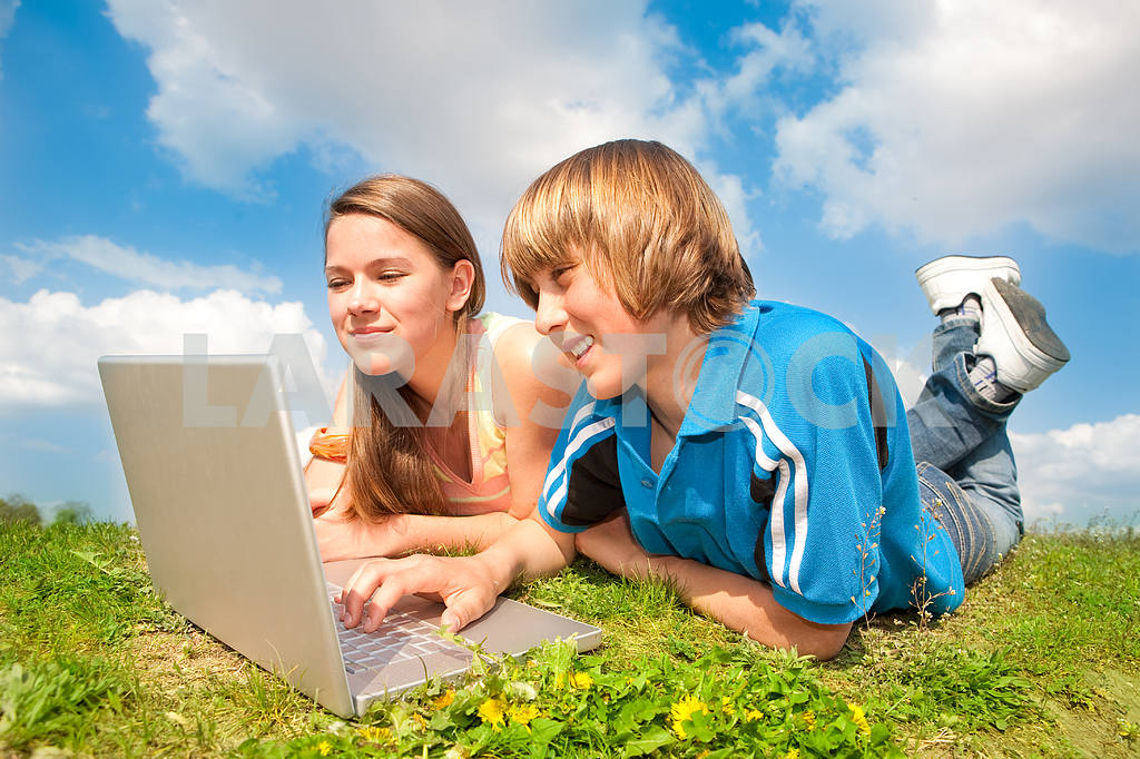 Two Smiling teenagers with laptop resting on meadow. — Image 11176