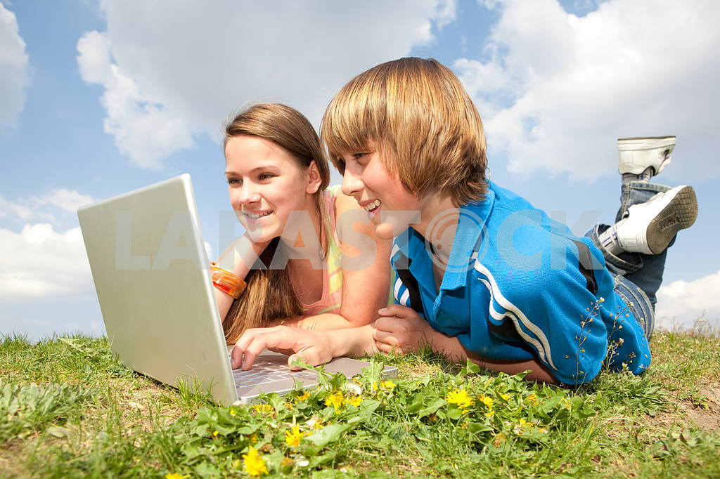 Two Smiling teenagers with laptop resting on meadow. — Image 11178