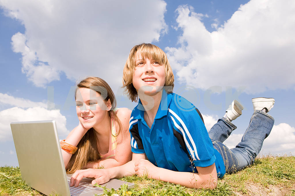 Two Smiling teenagers with laptop resting on meadow — Image 11180