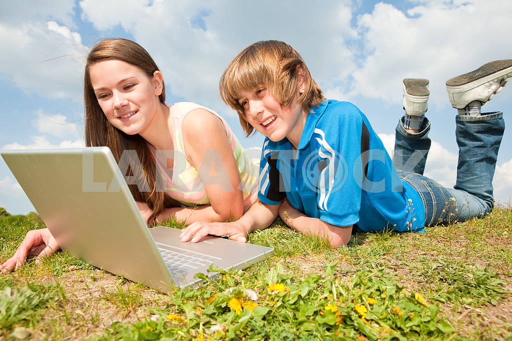 Two Smiling teenagers with laptop resting on meadow. — Image 11181
