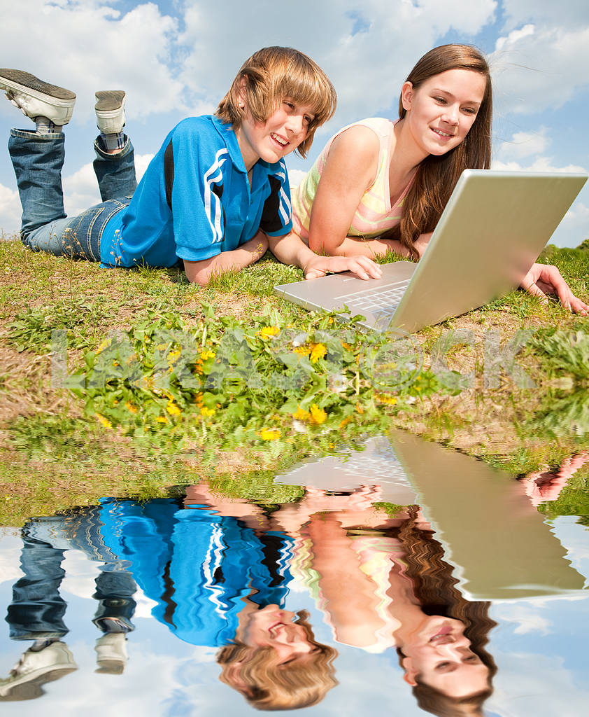 Two Smiling teenagers with laptop resting on meadow. — Image 11182