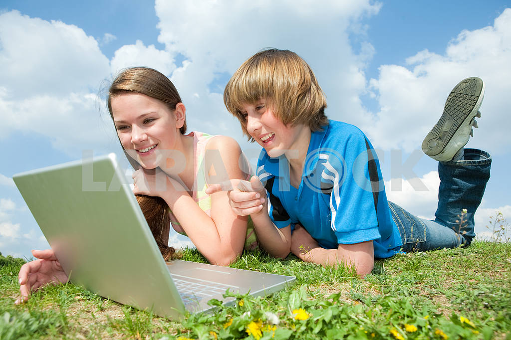 Two Smiling teenagers with laptop resting on meadow. — Image 11184
