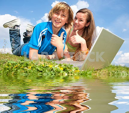 Two Smiling teenagers with laptop resting on meadow. Reflected i