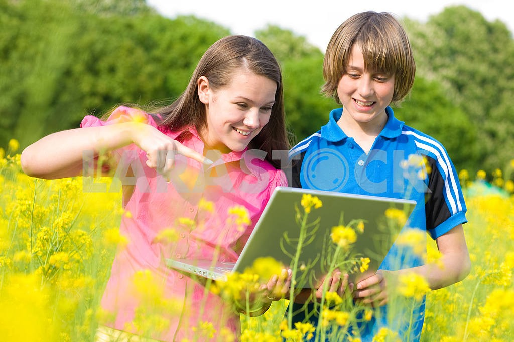 Two Smiling teenagers with laptop on meadow. — Image 11220