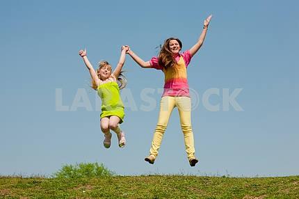Две девушки прыжки на зеленый луг