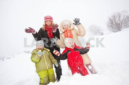 Portrait of happy mother and children together in snow on a cold