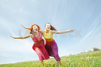 Funny mother and daughter on green grass