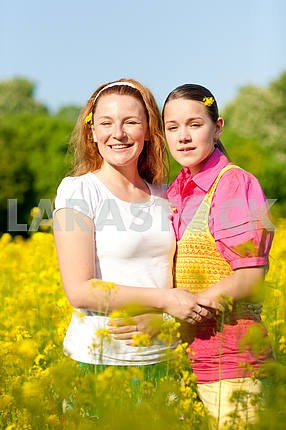 Mother and daughter on green meadow