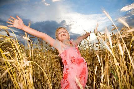 Little girl jumps in a wheat field