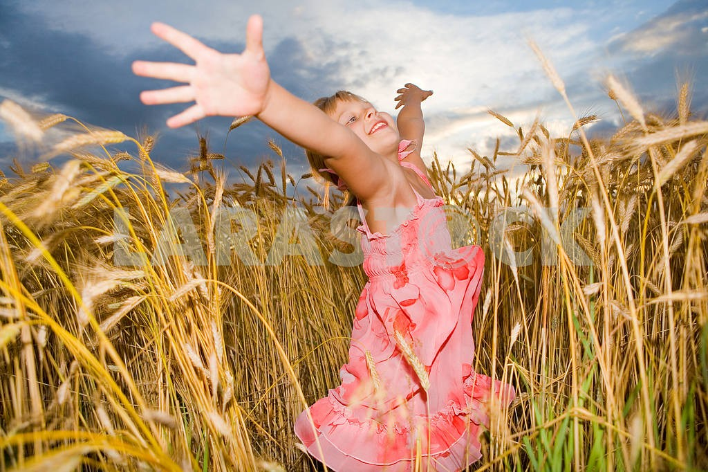 Little girl jumps in a wheat field. Against backdrop of cloudy s — Image 11605