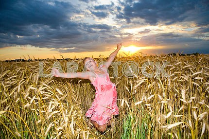 Little girl jumps in a wheat field. Against backdrop of cloudy s