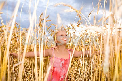 Little girl in a wheat field. Against the backdrop of blue sky.