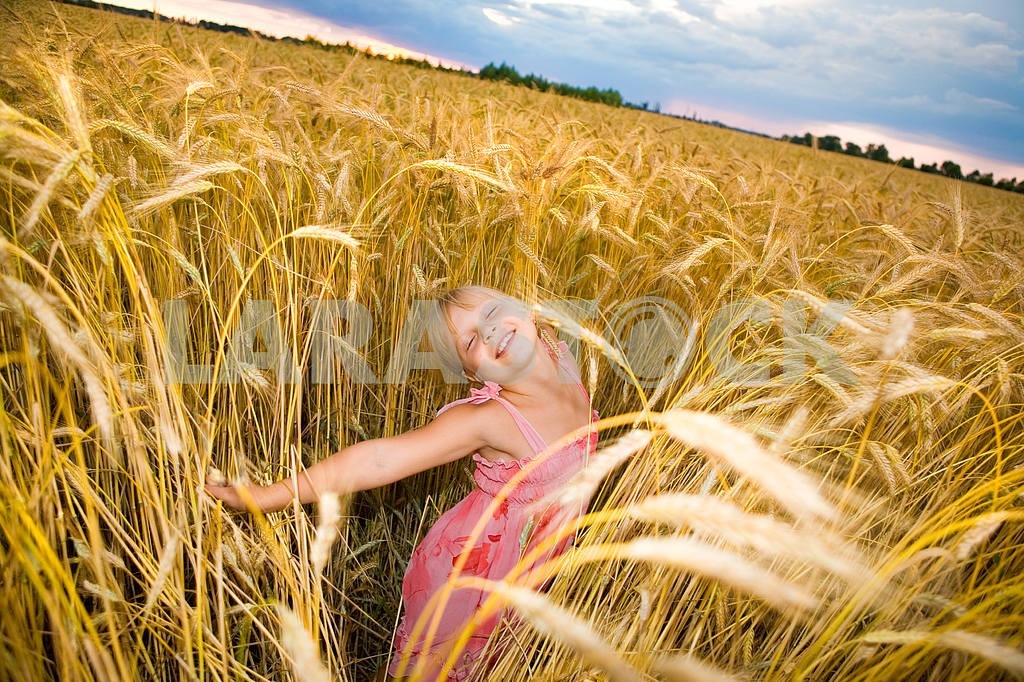 Little girl jumps in a wheat field. Against backdrop of cloudy s — Image 11613
