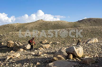 Man is walking along the rocky hill