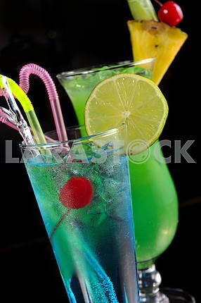 Green cocktail with pineapple and blue cocktail with ice and lim