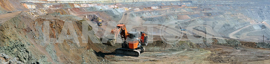 panorama of the iron ore quarry with an excavator