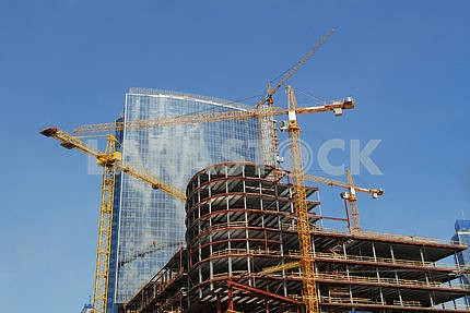 blue glass high rise tower with a crane