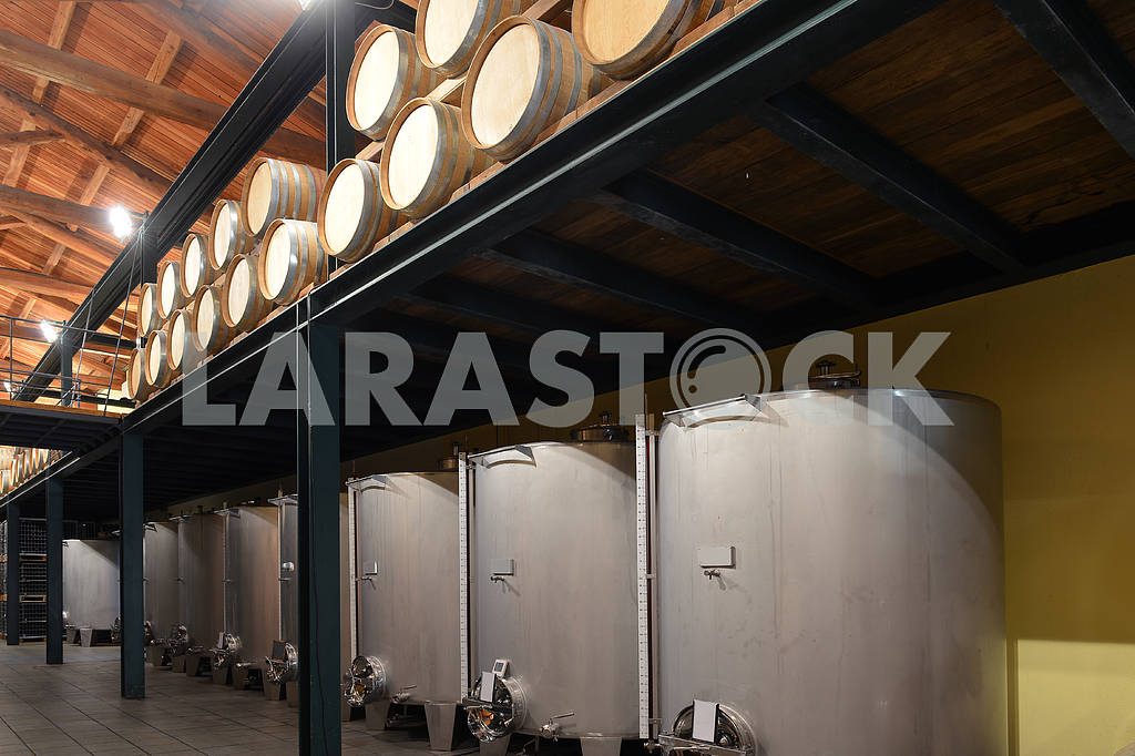 Stainless steel wine vats in a row inside the winery — Image 17671