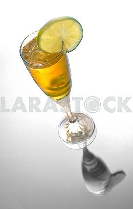Yellow cocktail in glass with lime