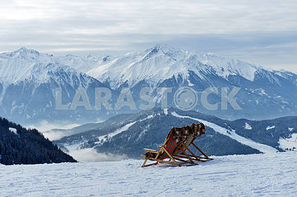 people in a chair on a background of mountains