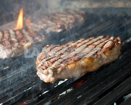 Стейк из говядины приготовления пищи на открытом гриле пламени