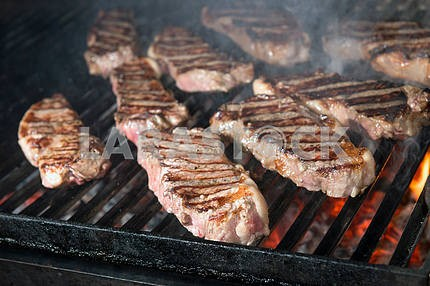 Beef steak cooking on an open flame grill
