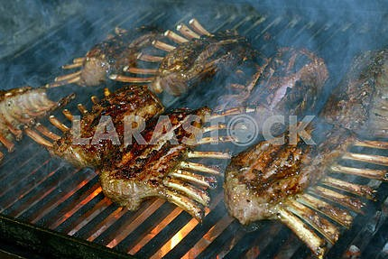 Rack of lamb frying on grill