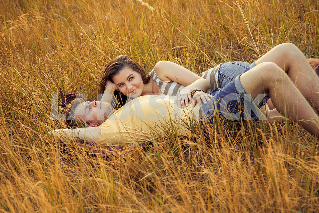 Young fashion beautiful loving casual style couple  lying down on floral field in autumnal park, warm sunny day, enjoying family, romantic date, happiness and love concept. — Image 19836