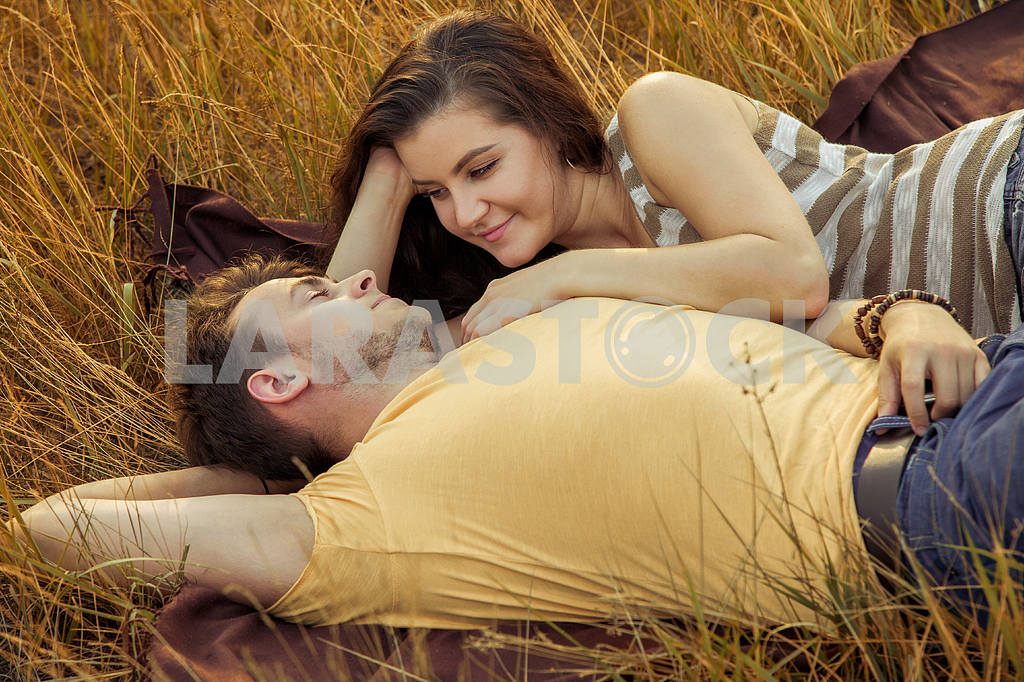 Young fashion beautiful loving casual style couple  lying down on floral field in autumnal park, warm sunny day, enjoying family, romantic date, happiness and love concept. — Image 19837
