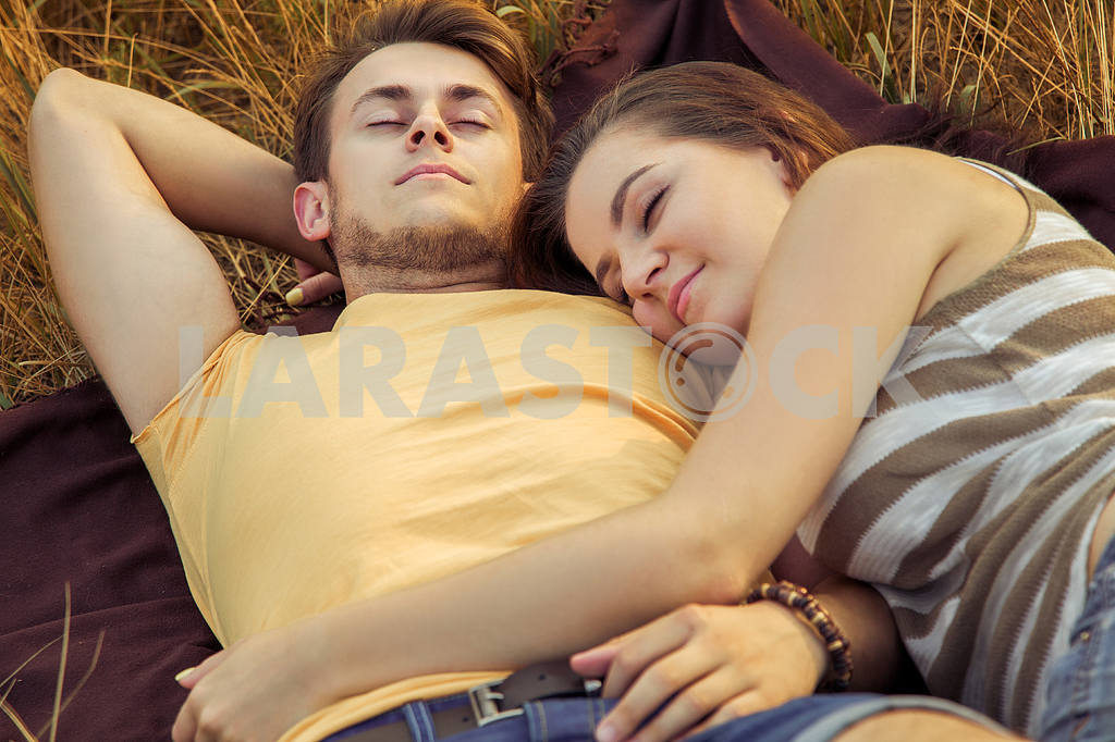 Young fashion beautiful loving casual style couple  lying down on floral field in autumnal park, warm sunny day, enjoying family, romantic date, happiness and love concept. — Image 19843
