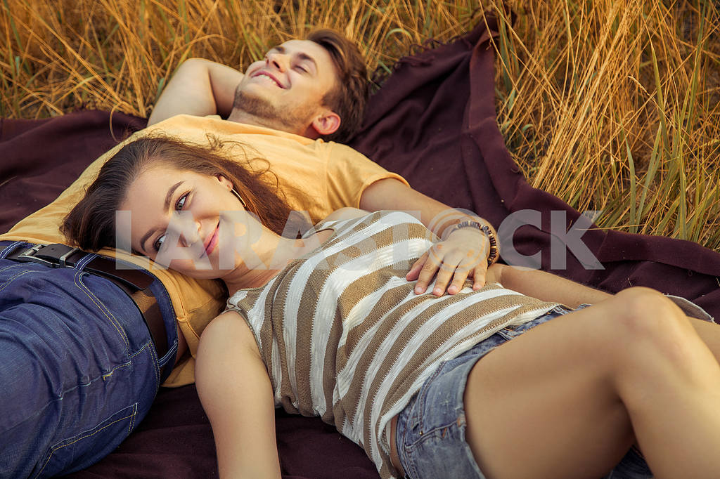 Young fashion beautiful loving casual style couple  lying down on floral field in autumnal park, warm sunny day, enjoying family, romantic date, happiness and love concept. — Image 19846